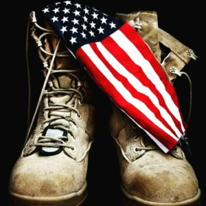 Military combat boots with American flag draped on them