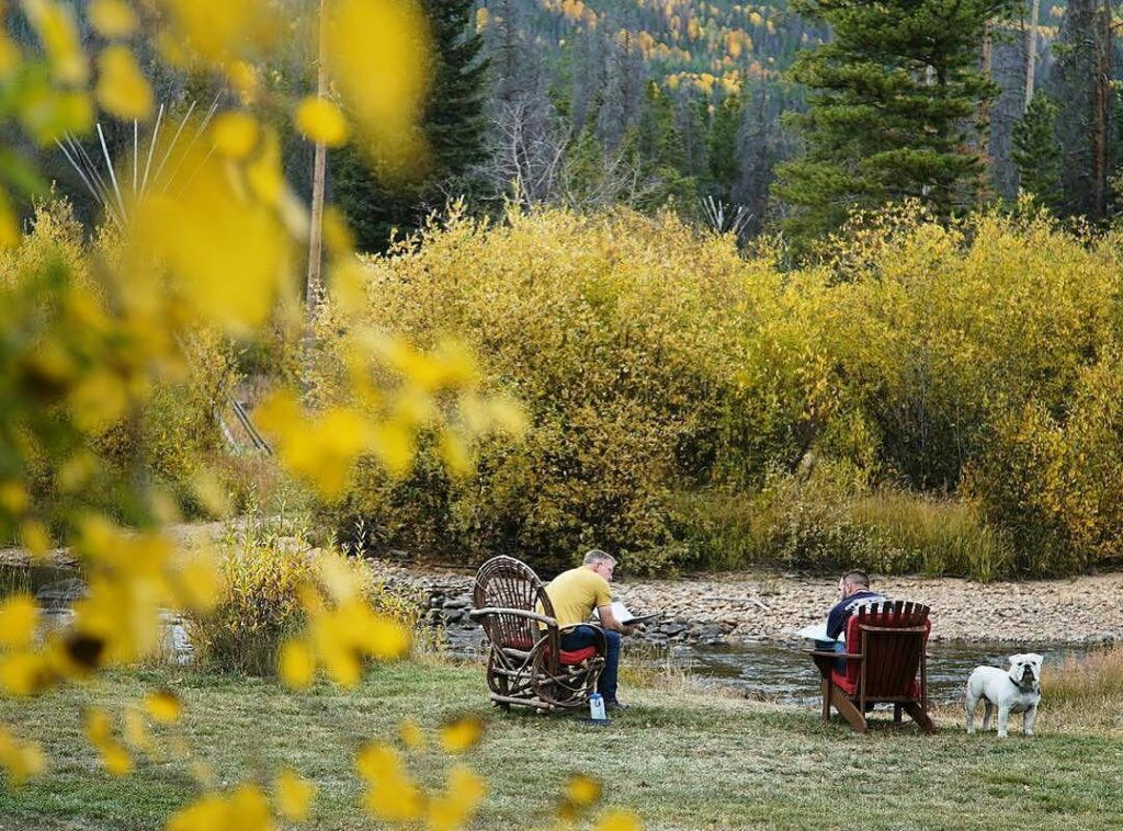 two men sitting by river talking in chairs