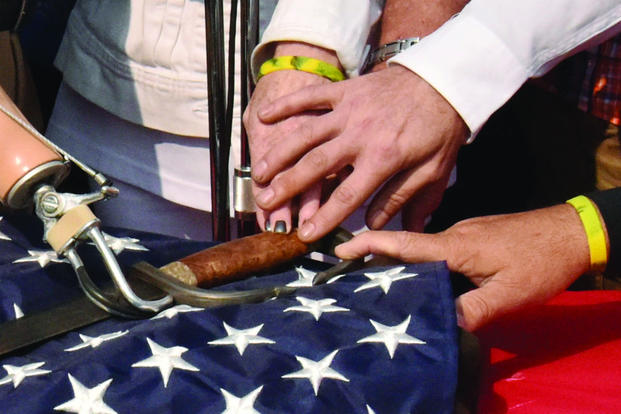 Spartan Pledge Sword on top of American flag with hands touching flag