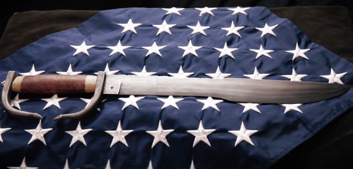 Spartan pledge sword laying on American flag