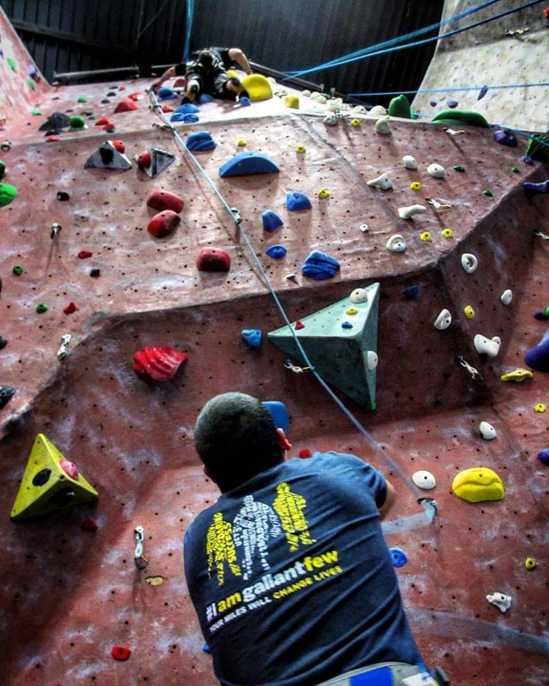 Back of rock wall climber wearing a GallantFew tee shirt