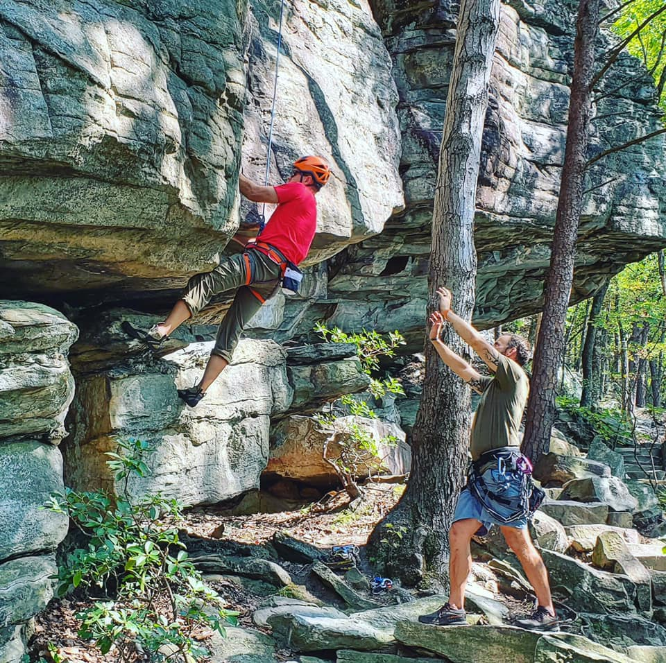 Two rock climbers belaying by a rock face