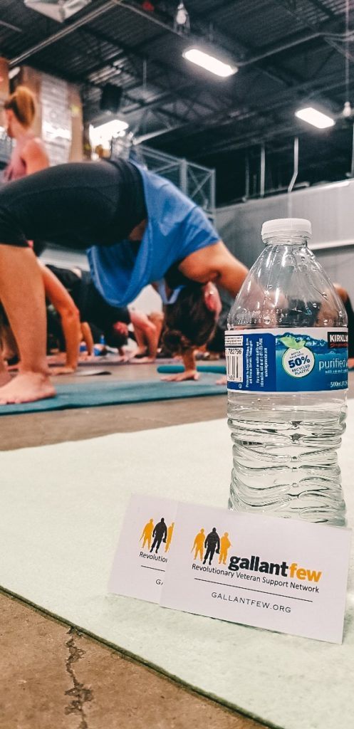 People doing yoga in background, GallantFew business card and water bottle in foreground