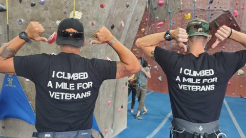 """Backs of climbers in front of rock wall, wearing shirts that say """"I climbed a mile for veterans"""""""