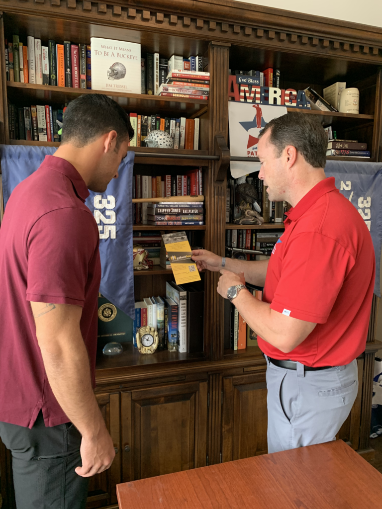 two guys talking over a GallantFew. brochure with bookshelf in background