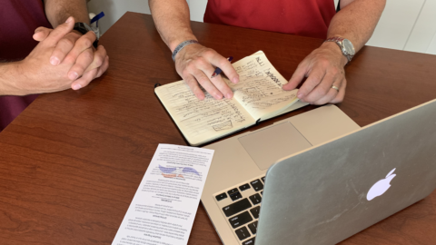 two people reviewing notebook, flyer and computer at a table. You cannot see their faces