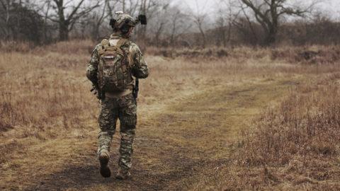 service member walking woodsy trail