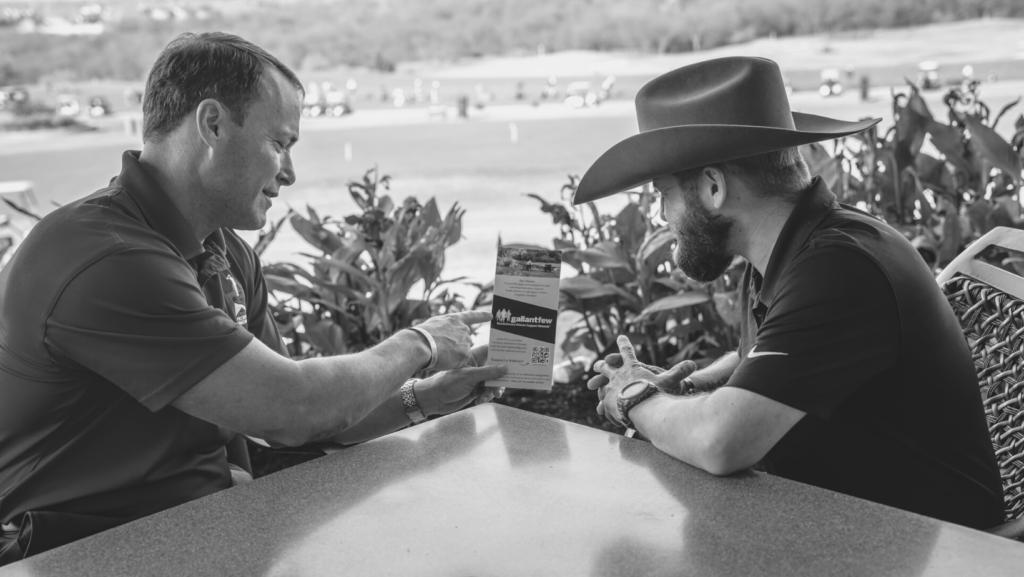 two men discussing brochure